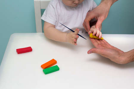 Boy playing with plasticine. Child molding modeling clay. Fine arts for toddler. Father and son together. Family time Reklamní fotografie