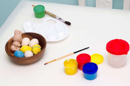 Painting Easter eggs, traditional holiday decoration. Art equipment closeup paint, palette and brush. Kids spring craft. Home Easter activity for family.