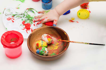 Child coloring wooden egg. Toddler Easter activity. Traditional holiday decoration. Art equipment paint, palette and brush. Reklamní fotografie