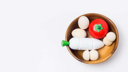 Wooden kids vegetable toys on White background. Healthy food concept. Game for development, eco and zero waste child products. Reklamní fotografie