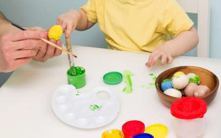 Child coloring wooden egg. Family Easter activity. Traditional holiday decoration. Art equipment paint, palette and brush.