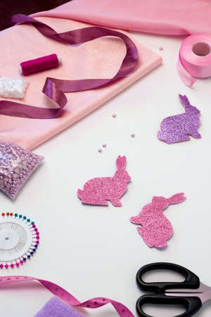Easter craft bunny tutorial. Accessories for needlework. Tools and Equipment Thread, tape and fabric. Beads, scissors and pins on white background. Reklamní fotografie