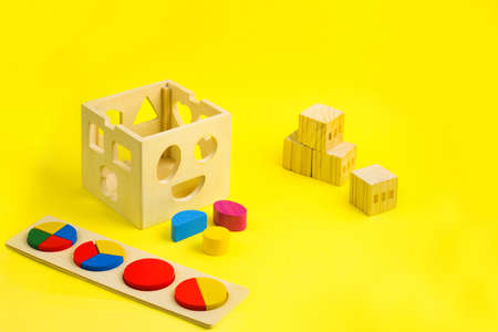 Development toys wooden puzzle, blocks and sorter on yellow