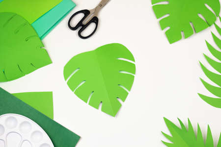 Jungle party decor top view. Handmade Hawaii decoration flatly. Paper cut out palm and monstera leaves craft. Reklamní fotografie