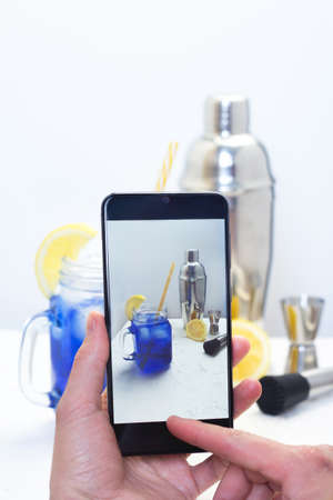 Hand with phone taking photo of coctail for blog. Bartender blogger filming video about bar accessories. Influencer with smartphone