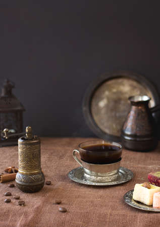 Traditional black coffee in vintage cup, retro mill and pot. Turkish delights oriental sweet dessert. Reklamní fotografie