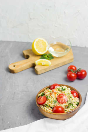 Traditional Arabic salad or Tabbouleh in wooden bowl, healthy vegetarian dish with couscous, tomatoes, parsley and mint. Lemon and olive oil on cement background Reklamní fotografie