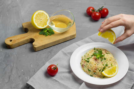 Traditional Arabic salad or Tabbouleh on white plate, healthy vegetarian dish with couscous, tomatoes, parsley and mint. Lemon and olive oil on cement background Reklamní fotografie