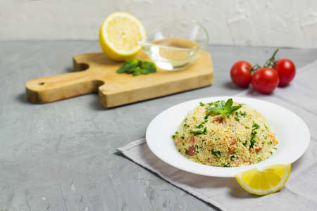 Traditional Arabic salad or Tabbouleh on white plate, healthy vegetarian dish with couscous on cement background