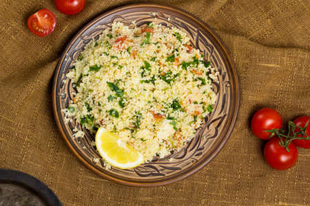 Traditional Arabic salad or Tabbouleh on ceramic plate, healthy vegetarian dish with couscous, tomatoes, parsley, mint