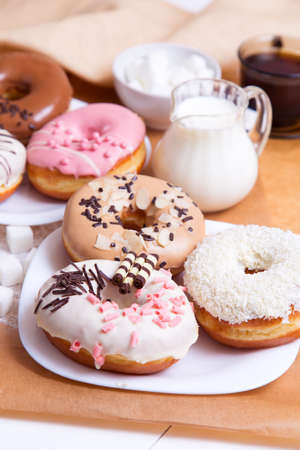 servilleta de papel: Colored donuts with glaze, coffee and milk on a white wooden background