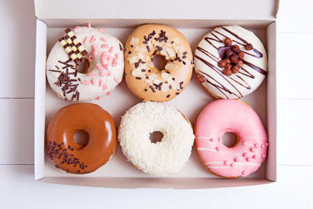 Colored donuts with glaze in a box on a white wooden background Stock Photo