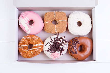 homemade cake: Colorful delicious donuts with sprinkles in a box on a white wooden background