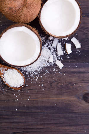 copyspace: Coconut halves with shell and shavings on a dark background. Top view with copyspace Stock Photo