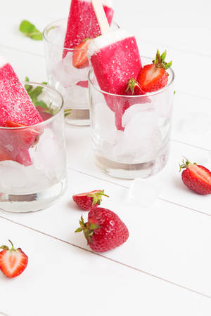 Homemade strawberry ice sticks in a glass with mint on a white wooden table Stock Photo