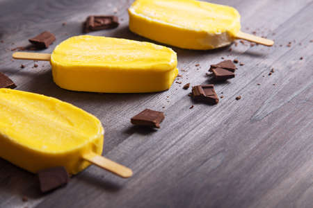 Yellow ice cream with chocolate bars and crumbs on dark wooden table. Space for text.