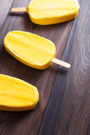 Yellow ice cream in a row on dark wooden table. Top view with copyspace
