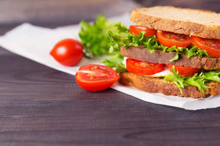 Homemade sandwich with egg, salad and tomatoes on crispy slice of rye bread on a dark wooden background