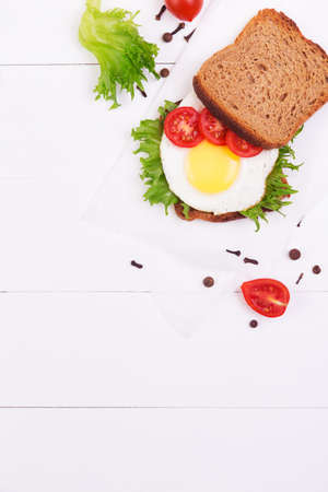whole wheat toast: Sandwich with egg, salad and tomatoes crispy slice of rye bread on a white wooden background. Top view with copyspace Stock Photo