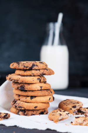 Chocolate chip cookies and bottle of milk with straw on dark grunge background. Space for text