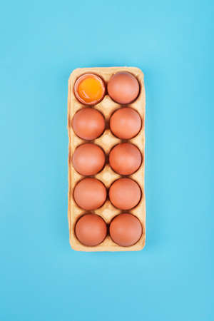 Natural organic chicken eggs in cardboard package on blue background. Top view with copyspace, flat lay.