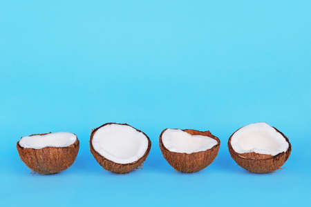 Halves of coconuts in peel on blue background. Flat lay minimal trendy photo with copyspace.