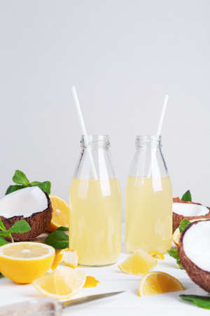 Fresh summer detox cocktail in glass bottles with coconut, lemon and mint on a light background. Space for text.