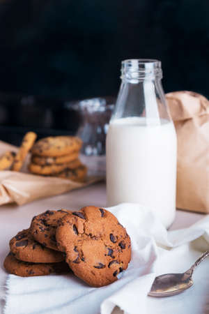 Homemade chocolate chip cookies with bottle of milk on napkin and dark grunge background. Space for text Stock fotó