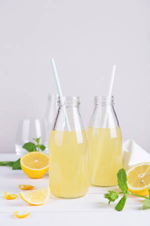 Fresh summer detox lemonade in glass bottles with lemon and mint on a light background. Space for text.