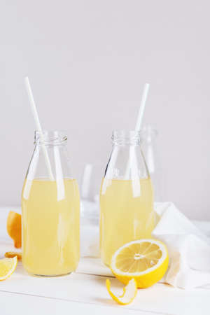 Glass bottles of fresh summer detox lemonade with lemon on a light background. Space for text. Stock fotó