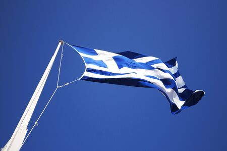 Greece flag flies on flagpole Stock Photo