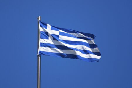 Flag of Greece on flagpole in sun Stock Photo