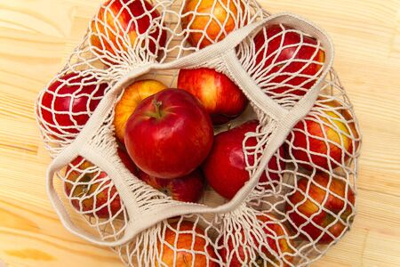 Cotton eco-friendly mesh bag with apples wood background Stock fotó