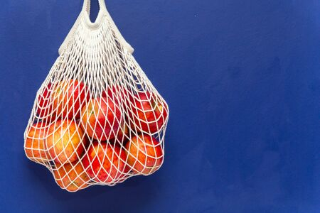 Red apples in a mesh cotton bag blue background Stock fotó