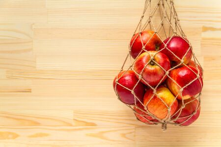 Eco-friendly jute rope mesh bag with apples wood background