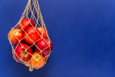 Handmade mesh bag and red apples blue background