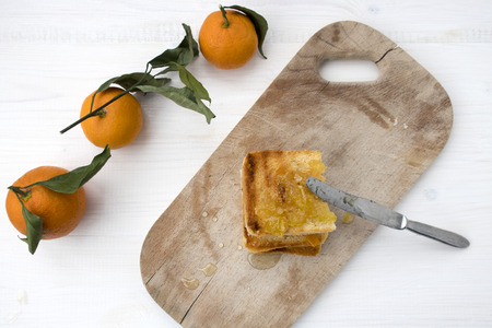 A sandwich with jam, a knife that spreads jam on a sandwich and tangerines on a light table. Banco de Imagens