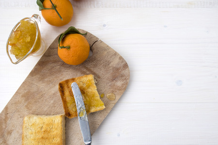 フルーツジャムと揚げパンにジャムを広げるナイフとスペースのコピーのための場所とサンドイッチ。 写真素材