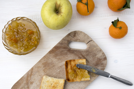 A sandwich with fruit jam and a knife that spread the jam on fried bread. Banco de Imagens
