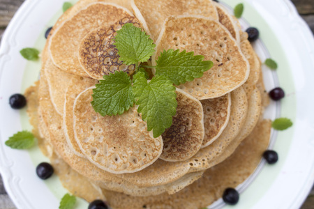 Green peppermint leaves are decorated with pancakes.