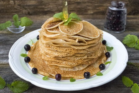 Pancakes are located in a plate on an old wooden table decorated with berries and mint leaves. Honey, which pour pancakes.