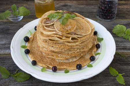 Pancakes are located in a plate on an old wooden table decorated with berries and mint leaves.  Stock Photo