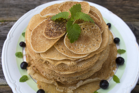 Large and small pancakes are located in a plate on an old wooden table decorated with berries and mint leaves. Close-up. Stock Photo