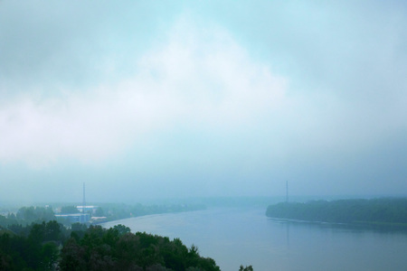 Cloudy and cloudy weather, rain and fog over the river.