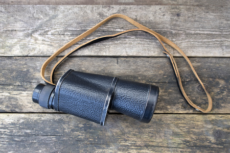 Old binoculars on a wooden background close-up