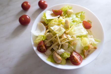 Appetizing and delicious dietary salad consisting of Peking cabbage, tomatoes, cheese, chicken pieces, croutons, located on a light background