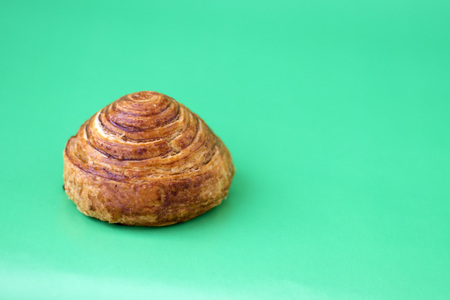 Bun with cinnamon close-up on a light green background and copy space