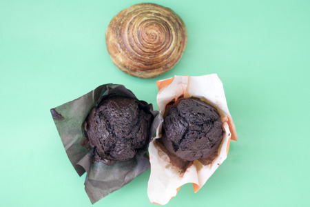Two chocolate muffins and a cinnamon roll on a green background close-up Stock Photo