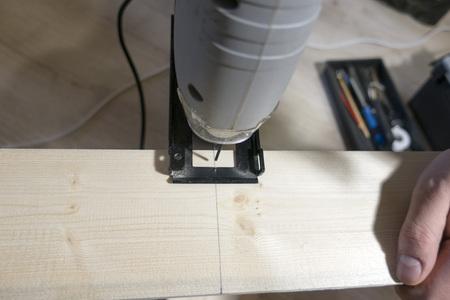 Electric jigsaw cuts a wooden board