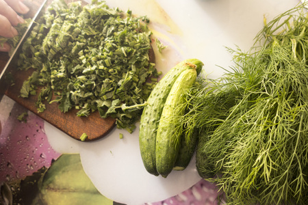 The hands of an elderly woman are cut with a knife freshly picked from the garden fresh mint, dill and fresh green cucumbers